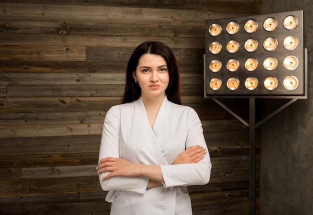 Portret van een vrouwelijke arts in een witte medische jurk op houten muur