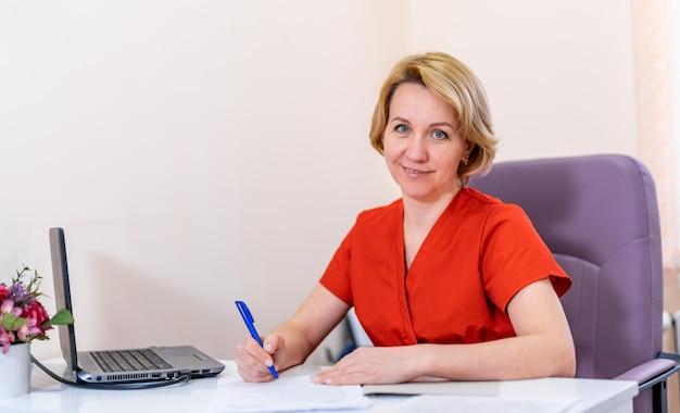 Portret van een vrouwelijke arts in het ziekenhuis. vrouw die naar de camera kijkt en glimlacht. moderne kantoor achtergrond.