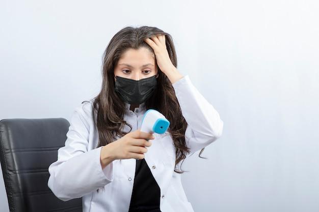 Portret van een vrouwelijke arts met een medisch masker en een witte jas die naar een thermometer kijkt.