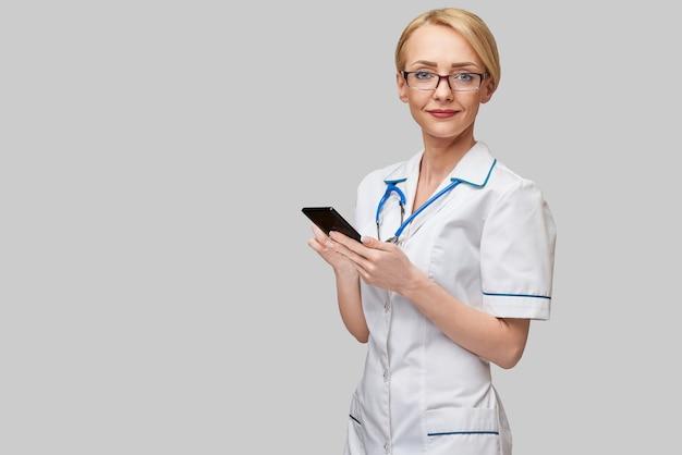 Portret van een vrouwelijke arts of verpleegster die mobiele telefoon houden en gebruiken