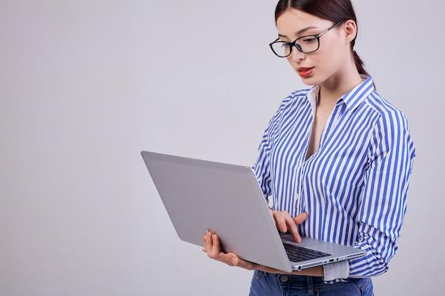 Portret van een vrouwelijke beheerder in een gestreept wit-blauw shirt met een bril en een laptop op grijs. werknemer van het jaar. hard werkende vrouw elke dag.