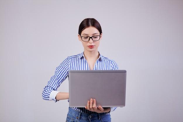 Portret van een vrouwelijke beheerder in een gestreept wit-blauw shirt met een bril en een laptop op grijs. werknemer van het jaar, zakelijke dame. bezig.