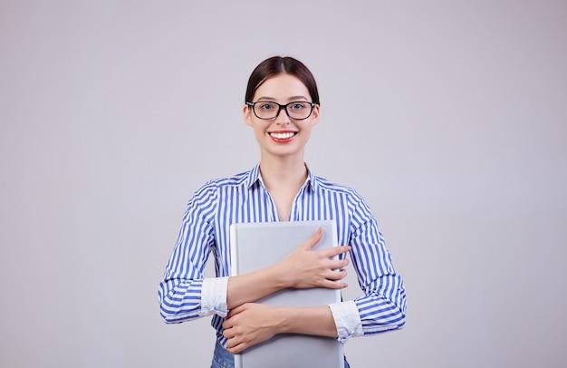 Portret van een vrouwelijke beheerder in een gestreept wit-blauw shirt met een bril en een laptop op grijs. werknemer van het jaar, zakelijke dame. drukke vrouw.