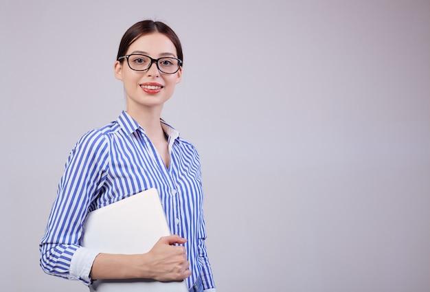 Portret van een vrouwelijke beheerder in een gestreept wit-blauw shirt met een bril en een laptop op grijs. werknemer van het jaar, zakelijke dame.