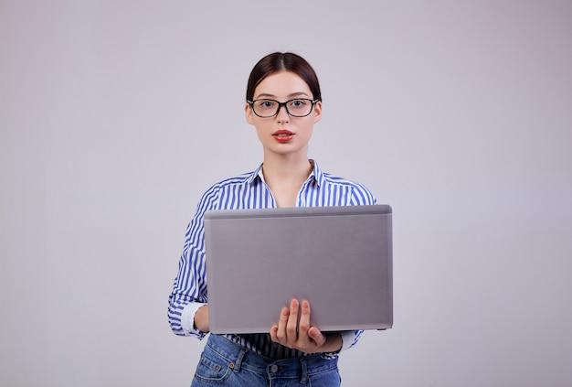 Portret van een vrouwelijke beheerder in een gestreept wit-blauw shirt met een bril en een laptop op grijs. werknemer van het jaar.