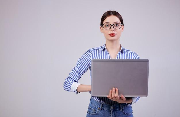 Portret van een vrouwelijke beheerder in een gestreept wit-blauw shirt met een bril en een laptop op grijs.