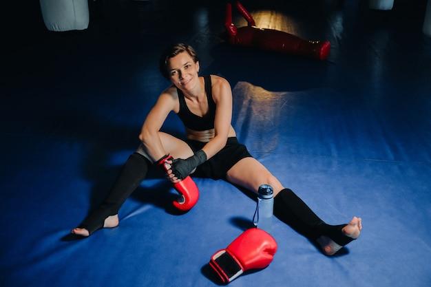 Portret van een vrouwelijke bokser in rode handschoenen in de sportschool na de training