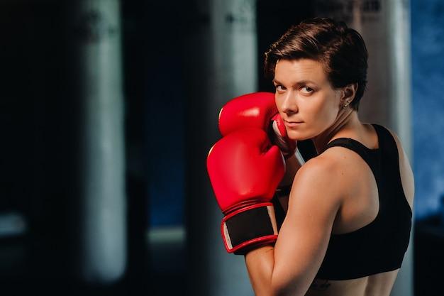 Portret van een vrouwelijke bokser in rode handschoenen in de sportschool tijdens de training
