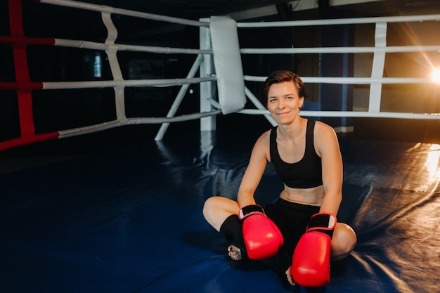 Portret van een vrouwelijke bokser met rode handschoenen na training zittend in de ring.