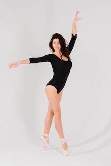 Portret van een vrouwelijke, dansende ballerina in een zwarte romper in de studio op een grijze achtergrond