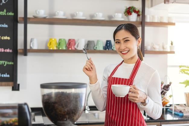 Portret van een vrouwelijke eigenaar die bij de poort van haar coffeeshop staat en een kopje koffie vasthoudt