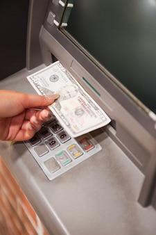 Portret van een vrouwelijke hand die dollars terugtrekt