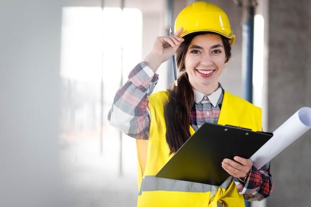 Portret van een vrouwelijke ingenieur op de bouwplaats en met een klembord in handen