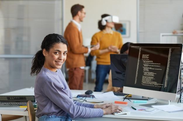Portret van een vrouwelijke it-ontwikkelaar die naar de camera kijkt en glimlacht tijdens het gebruik van een computer met code op het scherm in de softwareproductiestudio, kopieer ruimte
