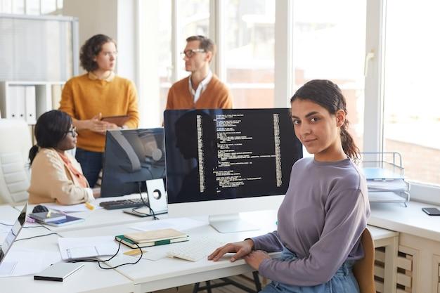 Portret van een vrouwelijke it-ontwikkelaar die naar de camera kijkt terwijl hij poseert tegen een computer met code op het scherm in de softwareproductiestudio, kopieer ruimte