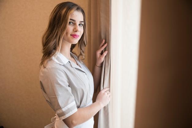 Portret van een vrouwelijke jonge kamermeisje gekleed in uniform camera kijken