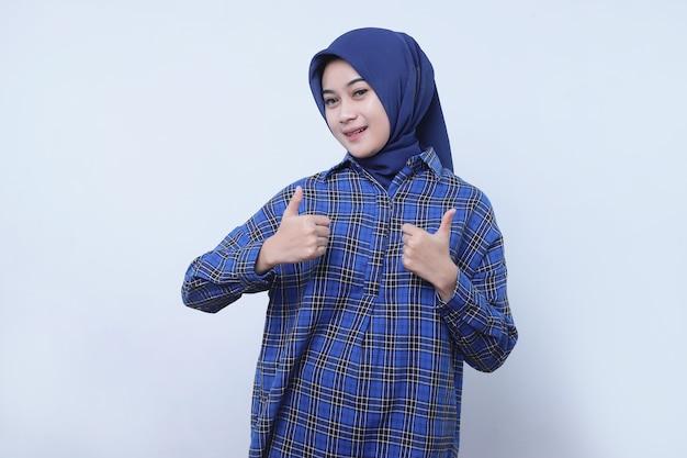 Portret van een vrouwelijke klant die steunt om gelukkig en gelukkig te zijn met het dragen van een hijab met duimen omhoog op een witte muur