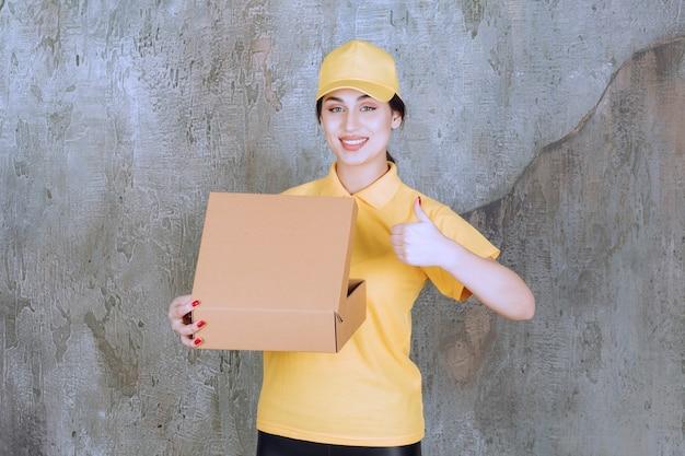 Portret van een vrouwelijke koerier die een kartonnen doos vasthoudt en duim omhoog laat zien