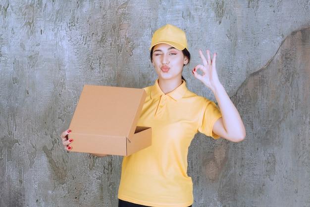 Portret van een vrouwelijke koerier die een kartonnen doos vasthoudt en een goed teken doet