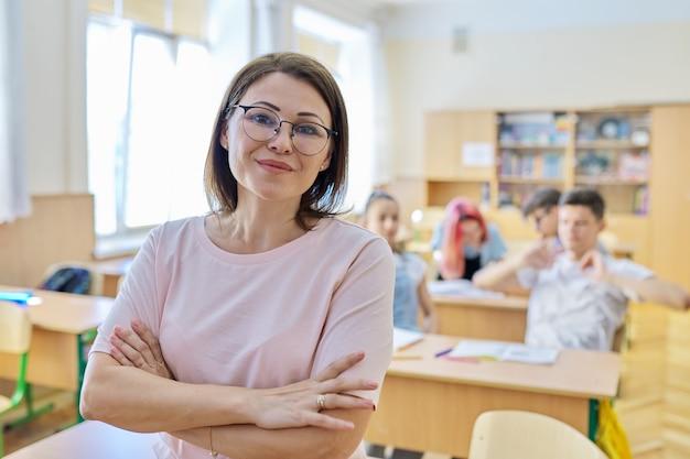 Portret van een vrouwelijke leraar van middelbare leeftijd in de klas, glimlachend zelfverzekerde vrouw met gevouwen handen die naar de camera kijkt, achtergrond van een klaslokaal met tienerstudenten