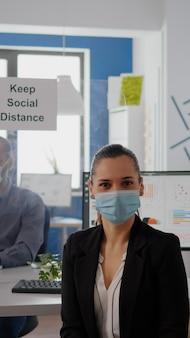 Portret van een vrouwelijke manager die een gezichtsmasker draagt om infectie met coronavirus te voorkomen, zittend op een stoel aan een bureautafel in een zakenkantoor. collega's houden sociale afstand met behulp van gescheiden plastic bord