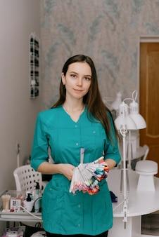 Portret van een vrouwelijke manicure met accessoires op grijs