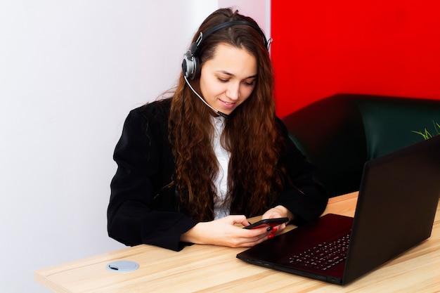 Portret van een vrouwelijke operator op een computer in een kantoor.