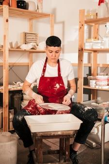 Portret van een vrouwelijke pottenbakker die de kleine tegels in de workshop schildert