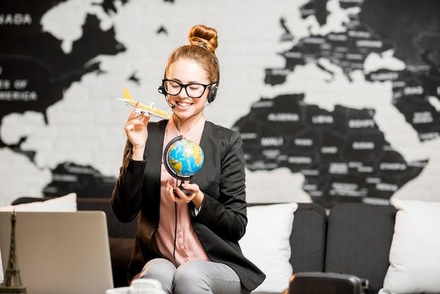 Portret van een vrouwelijke reisagent in pak en headset die speelt met globe en vliegtuig op de achtergrond van de wereldkaart