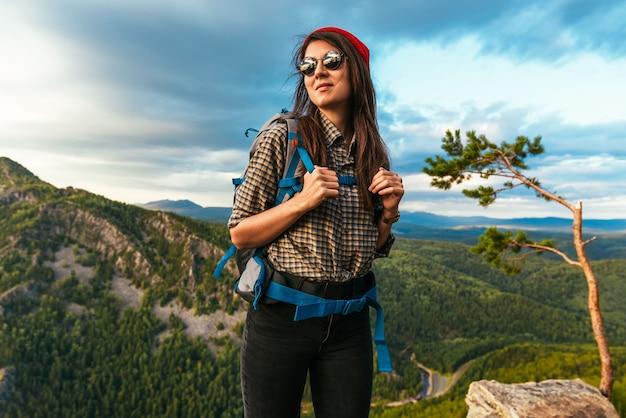 Portret van een vrouwelijke reiziger in de bergen. avontuur, reizen en wandelen concept. een gelukkige vrouw met een rode muts die geniet van het zonlicht tijdens een wandeling in de bergen. vrouwelijke toerist met bril
