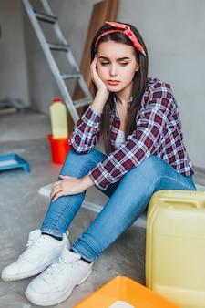 Portret van een vrouwelijke schilder die na het schilderen op de vloer bij de muur zit