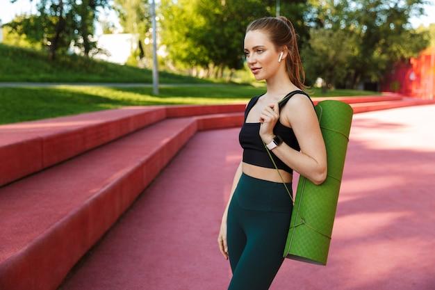 Portret van een vrouwelijke sportvrouw die een trainingspak en oordoppen draagt die een fitnessmat dragen tijdens een wandeling door het stadspark