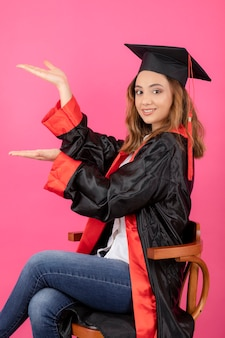 Portret van een vrouwelijke student die een afstudeerjurk draagt en haar handen omhoog houdt.