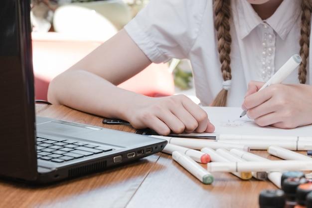 Portret van een vrouwelijke student die geniet van het leren in een coworking-kantoor met behulp van een laptopcomputer voor onderzoek, freelancer tijdens het maken van een project voor het maken van aantekeningen op afstand. leerling geconcentreerde tekennotities