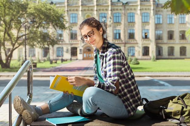 Portret van een vrouwelijke student met boeken over de achtergrond van de universiteit.