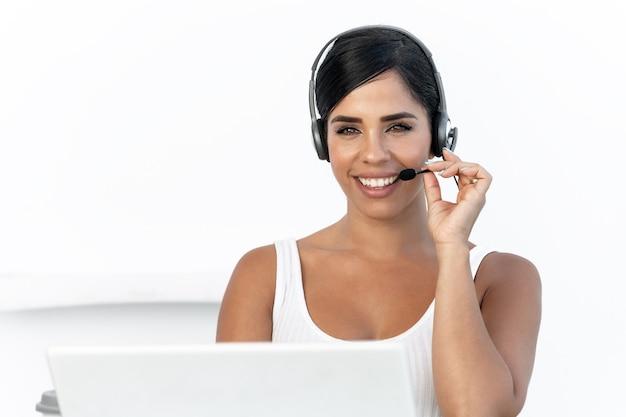 Portret van een vrouwelijke telemarketeer die naar de camera kijkt terwijl ze lacht met een witte achtergrond