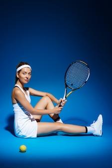 Portret van een vrouwelijke tennisser met racket en bal zittend op de vloer