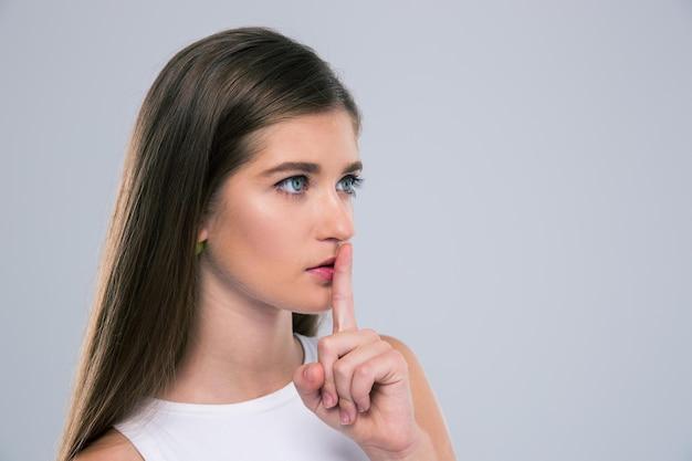 Portret van een vrouwelijke tiener die vinger over lippen geïsoleerd toont