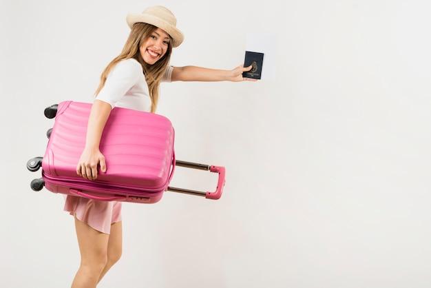 Portret van een vrouwelijke toerist die haar roze bagagezak draagt die paspoort toont tegen witte achtergrond