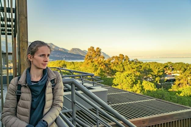 Portret van een vrouwelijke toerist die op het balkon staat en peinzend naar de buitenlucht kijkt