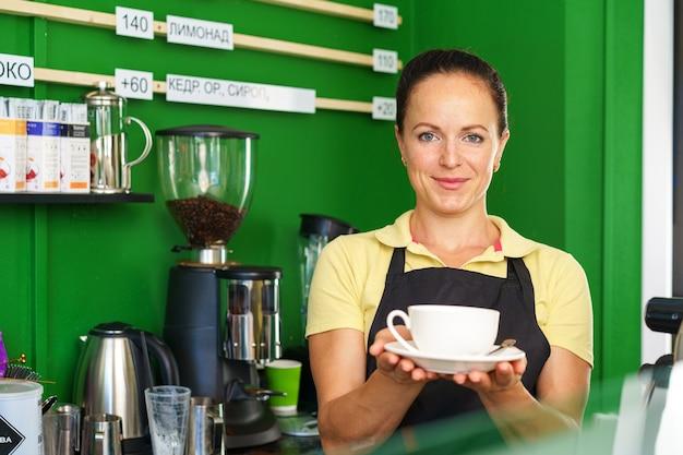 Portret van een vrouwenbarista in coffeeshop die zich bij balie bevindt