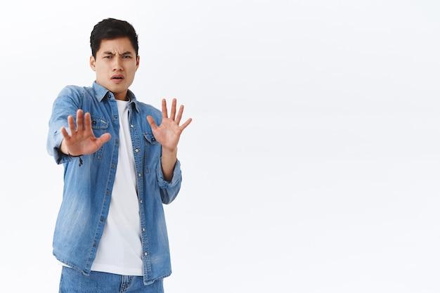 Portret van een walgelijke jonge aziatische man stapt achteruit en verdedigt zichzelf, trekt zich terug van walgelijk griezelig ding, grijnst ontevreden, drukt afkeer uit