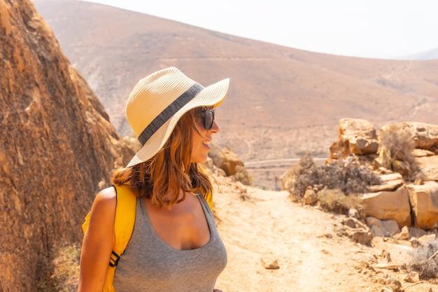 Portret van een wandelaarmeisje met een gele rugzak op het mirador de la peñitas-pad in de peñitas-canyon, fuerteventura, canarische eilanden. spanje