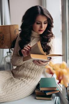 Portret van een warme sfeer close-up, jonge mooie vrouw droomt bij het raam, een boek lezen. getinte kleur.