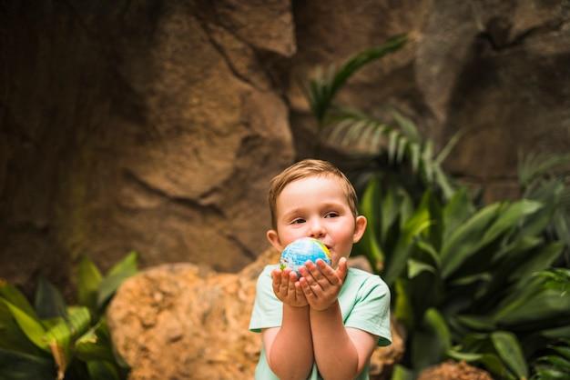 Portret van een wereldbol van de jongen in de hand te houden