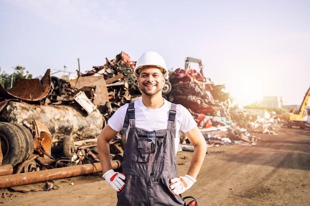 Portret van een werknemer die in de vuilnisbelt staat met een grote stapel verwijderd metaal op de achtergrond.
