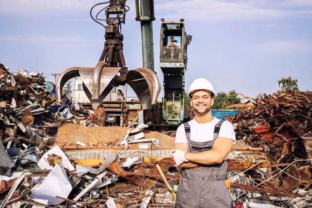 Portret van een werknemer die in een metalen schroothoop staat met een kraan die schroot opheft voor recycling.