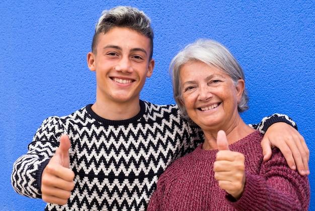 Portret van een witharige grootmoeder en tienerkleinzoon die lacht en omhelst terwijl ze naar de camera kijkt en een goed teken met handen doet. blauwe muur achtergrond