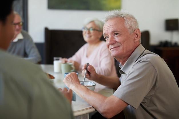 Portret van een witharige senior man die geniet van het ontbijt in de eetkamer in de kopieerruimte van het verpleeghuis