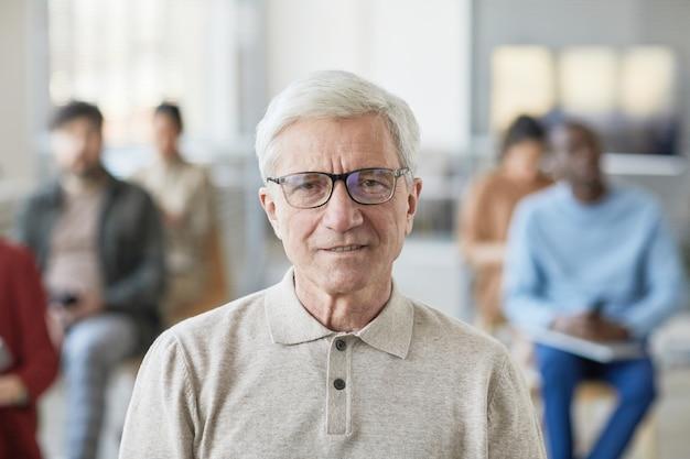 Portret van een witharige senior man die lacht naar de camera terwijl hij poseert in een kantooromgeving met mensen op de achtergrond, kopieer ruimte